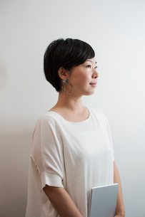 Profile view of woman with sort black hair wearing white shirt standing in art gallery.の写真素材 [FYI02261666]