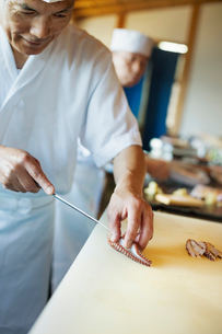Two chefs working at a counter at a Japanese sushi restaurant, slicing octopus tentacle.の写真素材 [FYI02261676]