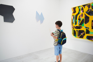 Boy with short black hair wearing backpack standing in art gallery, holding pen and paper, looking aの写真素材 [FYI02261689]