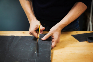 A man cutting a piece of grey fabric with shears.の写真素材 [FYI02261702]