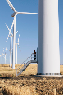 A wind farm technician standing and using a laptop at the base of a turbine on a wind farm in open cの写真素材 [FYI02261709]