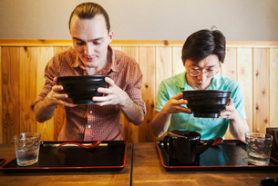 Two people in a noodle cafe lifting bowls of soba noodles. A western man and a Japanese man.の写真素材 [FYI02261716]