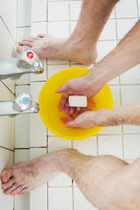 A man standing in a shower with soap in his hands, washing.の写真素材 [FYI02261717]