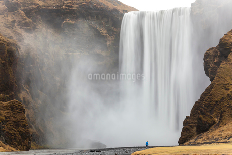 Landscape with rear view of person standing next to a tall waterfall.の写真素材 [FYI02261720]