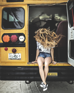 A young woman with long curly hair over her face sitting on the tailgate of a school bus.の写真素材 [FYI02261721]