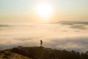 Rear view of man standing on top of mountain, admiring landscape view across misty valley.の写真素材 [FYI02261725]