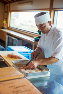 Chef working at a counter at a Japanese sushi restaurant, preparing fish in metal tray.の写真素材 [FYI02261735]