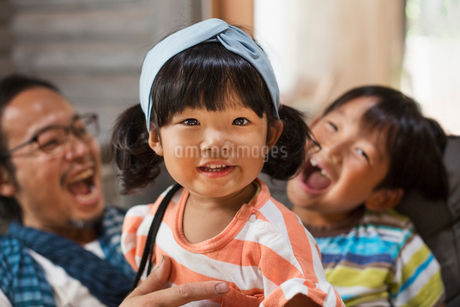 Man, boy and young girl with black pigtails wearing blue hairband sitting on a grey sofa, laughing.の写真素材 [FYI02261744]