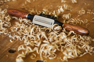 A traditional spokeshave with smooth wooden handles on wood covered with fresh curled wood shavings.の写真素材 [FYI02261747]