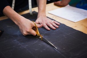 A man cutting a piece of grey fabric with shears.の写真素材 [FYI02261752]