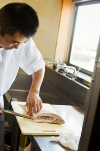 Chef working at a counter at a Japanese sushi restaurant, slicing fillet of fish.の写真素材 [FYI02261763]