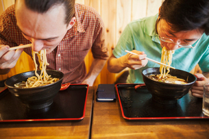 Two people in a noodle cafe eating bowls of soba noodles with chopsticks.の写真素材 [FYI02261769]