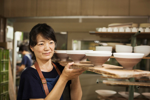 Woman standing in a Japanese porcelain workshop, carrying long wooden tray with bowls.の写真素材 [FYI02261770]