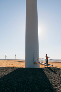 A wind farm technician standing and using a laptop at the base of a turbine on a wind farm in open cの写真素材 [FYI02261772]