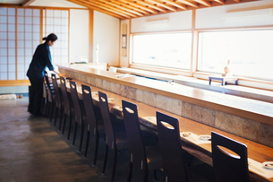 Waitress standing at a counter in a Japanese sushi restaurant, preparing place settings.の写真素材 [FYI02261776]