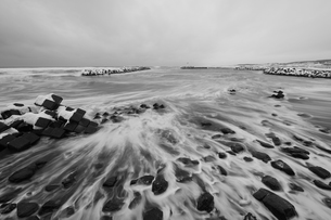 Snow-covered wave breakers on a rocky beach in winter.の写真素材 [FYI02261785]