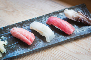 High angle close up of four pieces of sushi served on a rectangular dish.の写真素材 [FYI02261790]