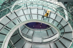 Interior view of building with person walking along glass and metal spiral staircase.の写真素材 [FYI02261803]