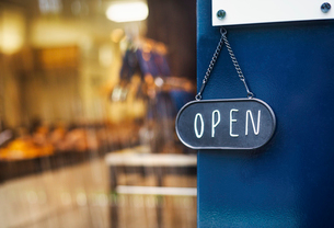 Close up of open sign on glass door to a bakery.の写真素材 [FYI02261811]