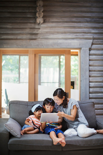 Woman, boy and young girl sitting on a grey sofa, looking at digital tablet.の写真素材 [FYI02261814]