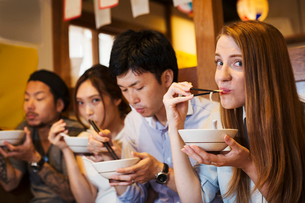 Four people sitting sidy by side at a table in a restaurant, eating from bowls using chopsticks.の写真素材 [FYI02261818]