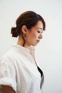 Profile view of woman with ponytail wearing white shirt standing in art gallery.の写真素材 [FYI02261836]