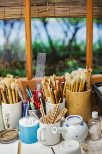 Close up of a selection of paintbrushes and tools in a Japanese porcelain workshop.の写真素材 [FYI02261852]