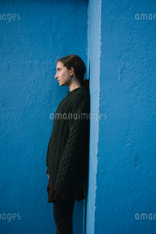 Portrait of teenage girl with brown hair in ponytail wearing black knitted jumper, leaning against bの写真素材 [FYI02261853]