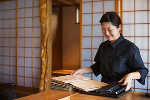 Smiling waitress standing at a counter in a Japanese sushi restaurant, holding menus.の写真素材 [FYI02261859]