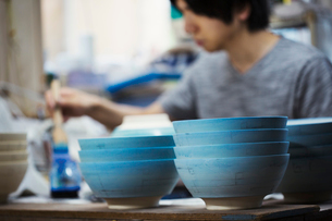 Close up of man working in a Japanese porcelain workshop, painting white bowls with blue glaze.の写真素材 [FYI02261861]