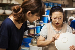 Two women standing in a Japanese porcelain workshop, inspecting a white bowl.の写真素材 [FYI02261863]