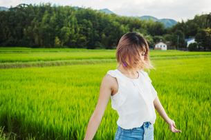A young woman in a white shirt and jeans with hands outstretched, standing in open space by rice padの写真素材 [FYI02261872]