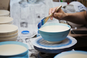Close up of person working in a Japanese porcelain workshop, painting white bowls with blue glaze.の写真素材 [FYI02261881]