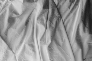 Black and white close up of wrinkled cotton sheets on bed.の写真素材 [FYI02261887]