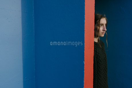 Portrait of teenage girl with brown hair in ponytail wearing black knitted jumper, leaning against bの写真素材 [FYI02261888]