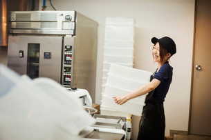 Woman working in a bakery, wearing baseball cap, carrying stack of white plastic crates.の写真素材 [FYI02261889]