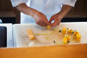 High angle close up of chef working at a counter at a Japanese sushi restaurant, preparing tofu rollの写真素材 [FYI02261895]