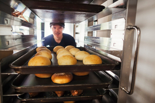 Man working in a bakery, placing large trays with freshly baked rolls on a trolley.の写真素材 [FYI02261903]