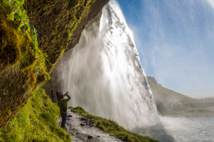 People standing on a narrow path underneath a waterfall cascade over a sheer cliff.の写真素材 [FYI02261907]