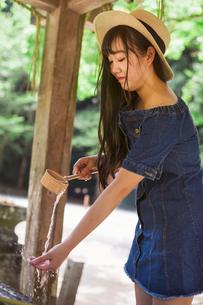 Young woman wearing blue dress and hat using bamboo water hand washing basins at Shinto Sakurai Shriの写真素材 [FYI02261919]