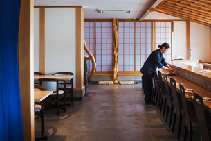 Waitress standing at a counter in a Japanese sushi restaurant, preparing place settings.の写真素材 [FYI02261928]