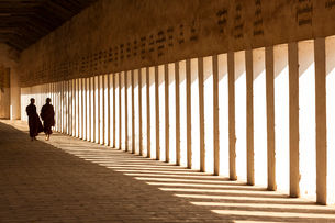 Rear view of two monks walking along sunlit colonnade of pagoda.の写真素材 [FYI02261957]