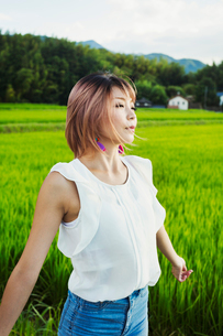 A young woman in a white shirt and jeans with hands outstretched, standing in open space by rice padの写真素材 [FYI02261972]