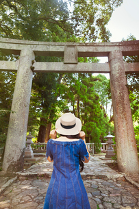 Rear view of young woman wearing blue dress and hat standing at Shinto Sakurai Shrine, Fukuoka, Japaの写真素材 [FYI02261980]