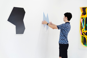 Side view of man with short black hair wearing blue shirt standing in art gallery, hanging modern paの写真素材 [FYI02261995]