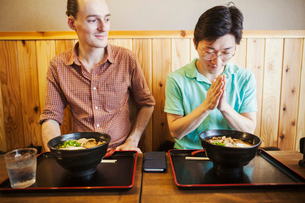 A western man in a noodle restaurant, observing his Japanese companion with hands in prayer, makingの写真素材 [FYI02262004]