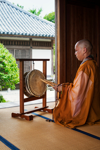 Side view of Buddhist monk with shaved head wearing golden robe kneeling in front of drum inside temの写真素材 [FYI02262014]