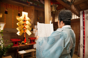 Rear view of priest holding scroll at Shinto Sakurai Shrine, Fukuoka, Japan.の写真素材 [FYI02262030]
