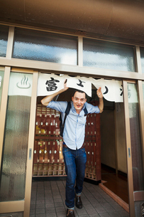 A young Western man coming out of a public bath house, ducking under the entrance sign.の写真素材 [FYI02262038]