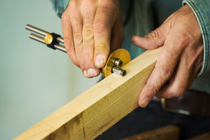 A craftsman using a measuring guage on a piece of fresh wood.の写真素材 [FYI02262039]